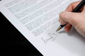 Photo of person signing legal document
